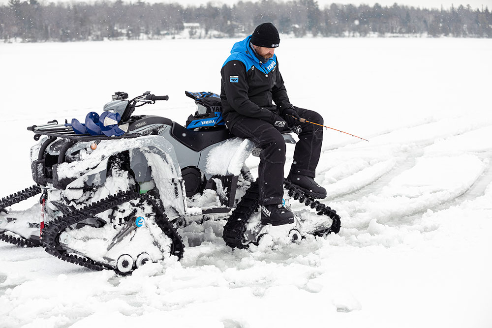 ATV with track kit and man fishing on ice