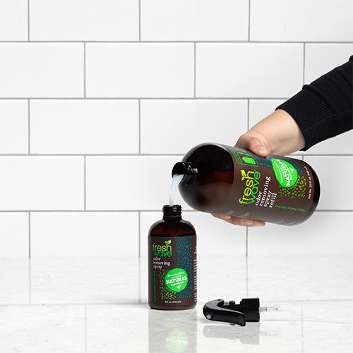 Fresh Wave Odor Removing Spray Refill Pouring into a Fresh Wave 8 oz. Spray Bottle