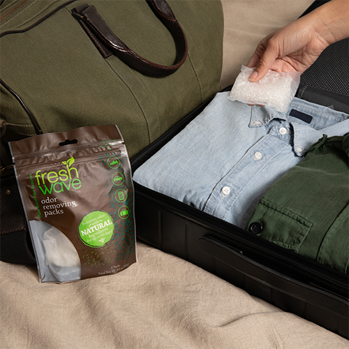 Fresh Wave Odor Removing Packs Being Packed in Suitcase with Clothes